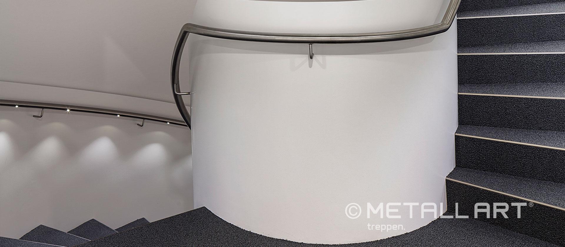 Weiße Betontreppe mit Metallhandlauf